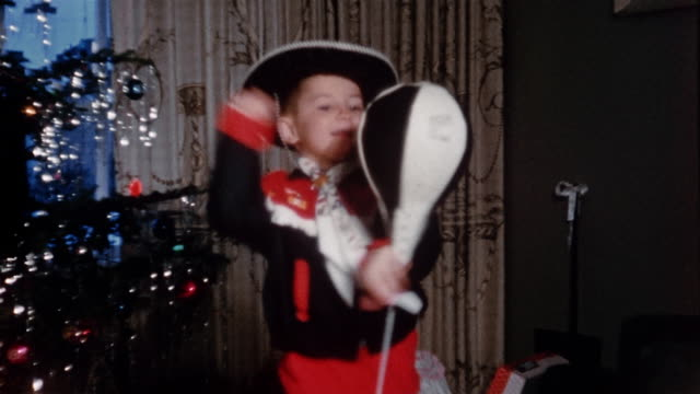 stockvideo's en b-roll-footage met 1950s medium shot young boy in cowboy costume punching bag in living room / part of christmas tree in background - stootzak fitnessapparatuur