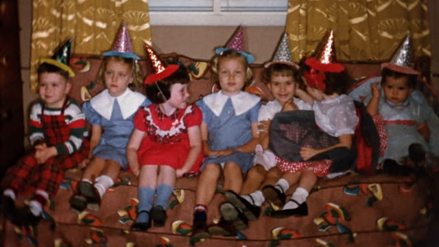 1950s medium shot young girls in party hats sitting on couch and smiling at cam at party - home movie stock videos & royalty-free footage