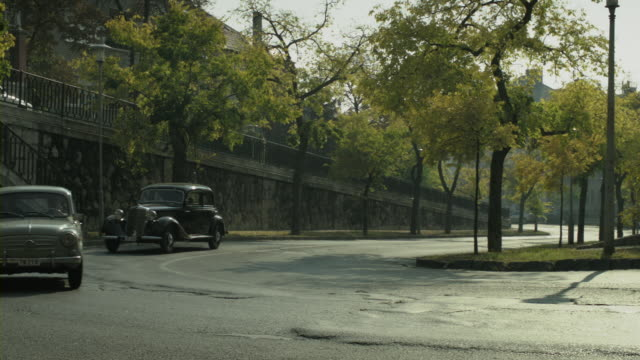 a 1950s mercedes benz and a cabriolet 170s drive around a curved residential street in budapest. - budapest stock videos & royalty-free footage