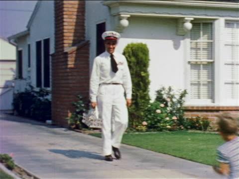 1950s pan milkman carrying basket walking down driveway passing children on suburban street - milkman stock videos & royalty-free footage