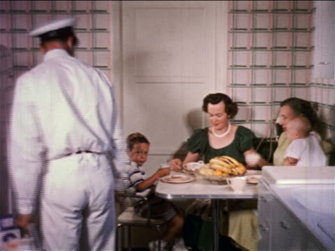 1950s milkman closing refrigerator + talking to boy in kitchen / two women + baby sitting at table - milkman stock videos & royalty-free footage