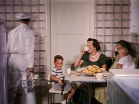 1950s milkman exiting kitchen with two women, boy + baby at table / educational - milkman stock videos & royalty-free footage