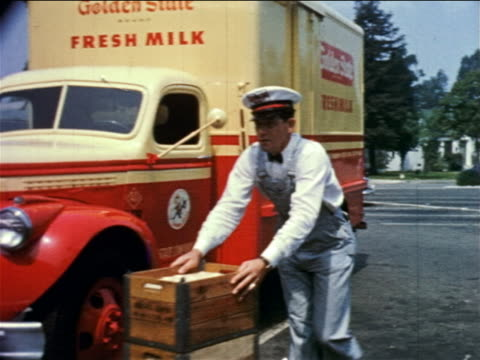 1950s milkman in uniform pushing cart of crates of milk past parked milk truck / educational