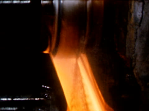 1950s molten steel running through rollers during bloom casting process in steel mill / audio