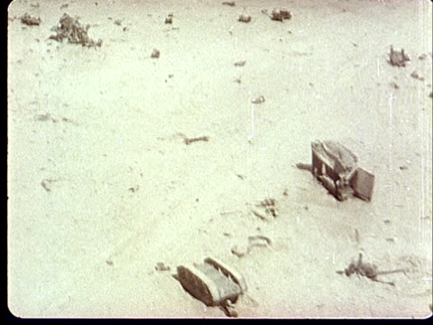 1950s montage aerial ts wreckage from explosion in desert / army tank halfburied in sand at camp desert rock at nevada test site / nye county nevada... - campo militare video stock e b–roll