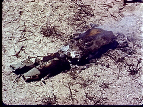 1950s montage ms dummy of soldier lying face first in sand / cu burning scrap from atomic explosion / dummy soldier lying w/ rifle in trench /... - campo militare video stock e b–roll
