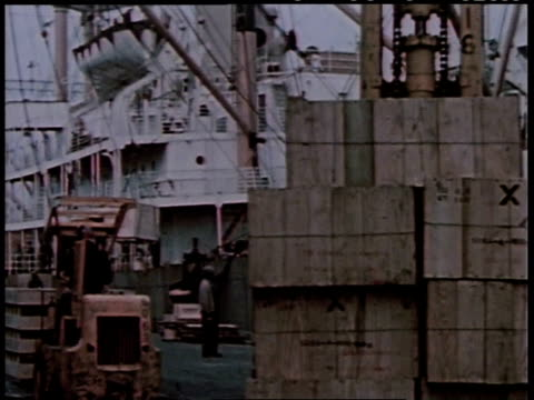 1950s montage large crates being loaded onto a freighter / united states - beladen stock-videos und b-roll-filmmaterial