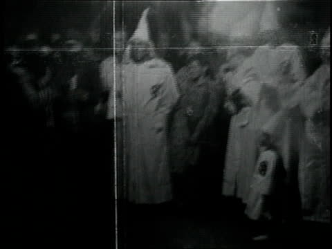 vídeos de stock, filmes e b-roll de 1950s montage meeting of the kkk in front of burning cross / georgia united states - ku klux klan