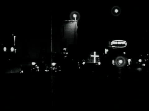 1950s montage night car parade of kkk members with a lit cross on the front bumper of one of the cars / georgia united states - クー・クラックス・クラン点の映像素材/bロール
