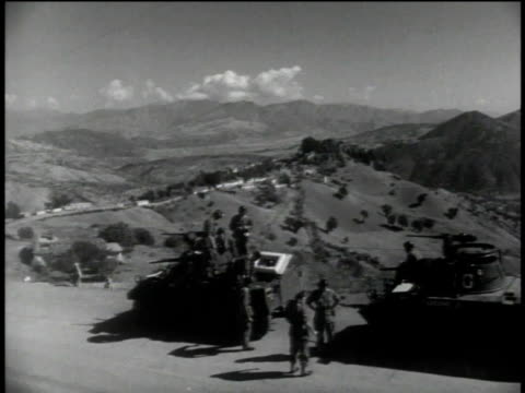1950s montage soldiers and tanks standing on dirt road in rugged country - esercito militare francese video stock e b–roll