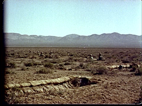 1950s montage ws soldiers ducking down into trenches at camp desert rock at nevada test site / nye county nevada usa - campo militare video stock e b–roll