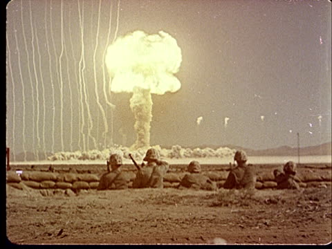 1950s MONTAGE POV Soldiers hiding inside trench / Soldiers standing up / PAN Atomic bomb exploding / Mushroom cloud forming and sending shockwaves at...