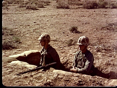 1950s montage soldiers in pairs waiting in trenches / soldier smoking cigarette / men joking at camp desert rock at nevada test site / nye county... - campo militare video stock e b–roll