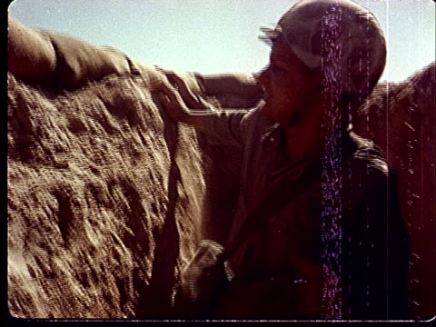 1950s montage soldiers standing up in trenches and getting hit by gust of sand from shockwave of explosion at camp desert rock at nevada test site /... - nevada stock-videos und b-roll-filmmaterial