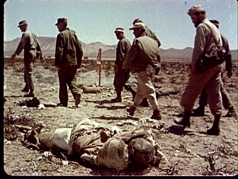 1950s montage ms soldiers walking by and looking back at dummy soldier lying in desert / ws soldiers walking by and looking over at small fire in... - campo militare video stock e b–roll