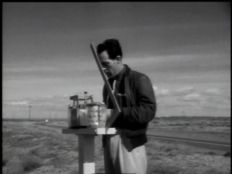 1950s MONTAGE technician checking monitoring equipment in a field / Hanford, Washington, United States