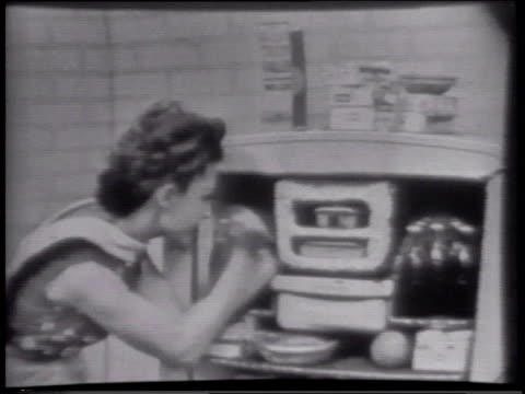 1950s montage woman demonstrating how to defrost freezer in westinghouse commercial. betty furness showing off westinghouse refrigerator, but the door won't open. camera zooms in tight on her face while someone offscreen opens it for her. - ausrutscher stock-videos und b-roll-filmmaterial
