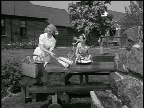 vidéos et rushes de b/w 1950s mother + daughter setting picnic table / boy + father in background - pique nique