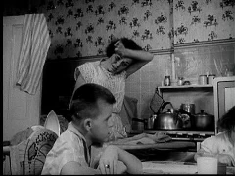 """""""1950s ms mother doing ironing in cramped kitchen as kids sit at table/ st. louis, missouri/ audio"""" - stay at home mother stock videos & royalty-free footage"""