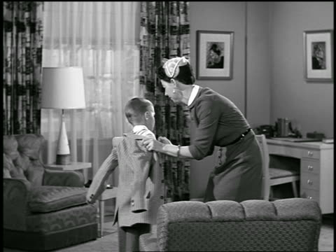 b/w 1950s mother helping son put on jacket + baseball cap in living room - baseballmütze stock-videos und b-roll-filmmaterial