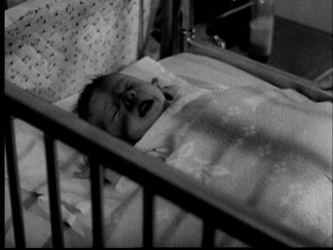 "vidéos et rushes de ""1950s cu newborn baby crying in crib/ tu ms nurse picking up baby/ st. louis, missouri"" - nouvelle vie"