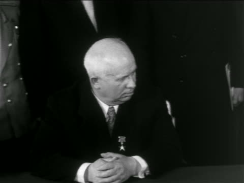 B/W 1950s Nikita Khrushchev sitting at table looking to side / newsreel