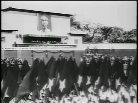 B/W 1950s people carrying flags in parade past building with poster of Ho Chi Minh / North Vietnam