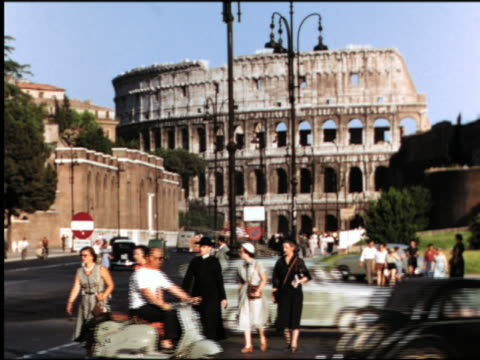 1950s people crossing street with traffic in front of colosseum / rome, italy - rome italy stock-videos und b-roll-filmmaterial