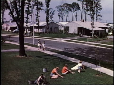 1950s HA People relaxing on lawn in quiet residential neighborhood / Levittown, Pennsylvania, United States