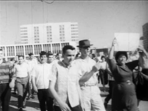 B/W 1950s people walking at demonstration with signs Confederate flags / New Orleans low angle / newsreel