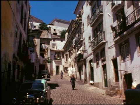 1950s people walking down narrow sloping village street with parked cars / portugal - portugal stock-videos und b-roll-filmmaterial