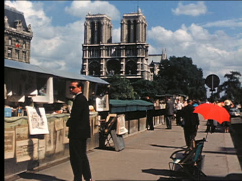 1950s people walking on sidewalk + looking at sidewalk vendor stands / notre dame in background / paris - 1950 stock videos & royalty-free footage