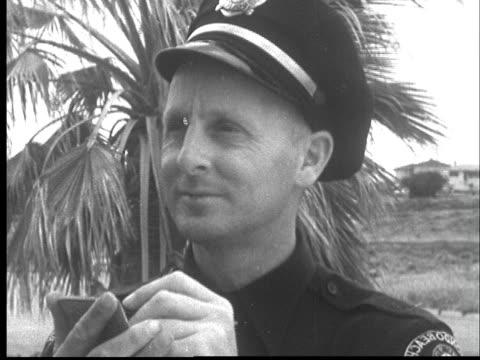 "vídeos de stock, filmes e b-roll de ""1950s cu police officer looking up from note pad nodding head/ redondo beach, california/ audio"" - note pad"