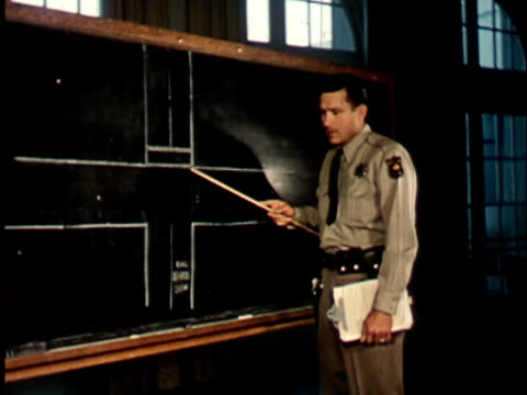 1950s MS, Police officer pointing at intersection drawn on blackboard, Berkeley, California, USA