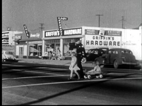 """1950s WS Police officer stopping traffic for little girl pulling other girl across street in wagon/ Redondo Beach, California/ AUDIO"""