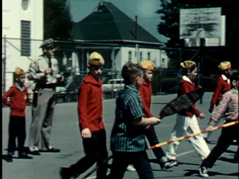 1950s MS, PAN, Police officer supervising group of boys (12-13) with stop signs on street, Berkeley, California, USA