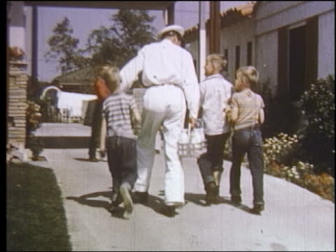1950s rear view children walking up driveway with milkman making delivery / educational - milkman stock videos & royalty-free footage