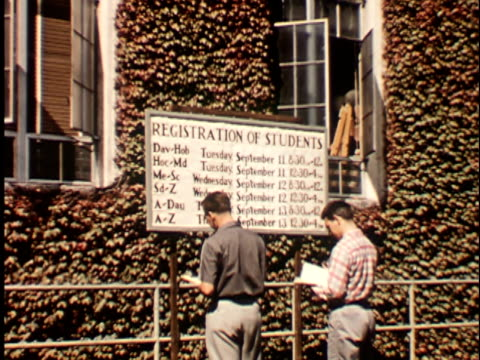 1950s MS, ZI, CU, Rear view of two male students at Registration of Students board at Berkeley University, 1950's, California, USA