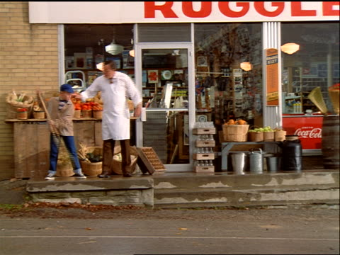 1950s reenactment of boy sweeping outside grocery store + boss showing him how to do a better job - bossy stock videos & royalty-free footage
