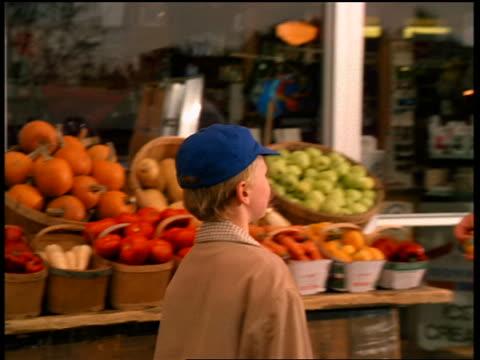 1950s reenactment of boy walking toward + talking to grocer in front of grocery store - lebensmittelhändler stock-videos und b-roll-filmmaterial