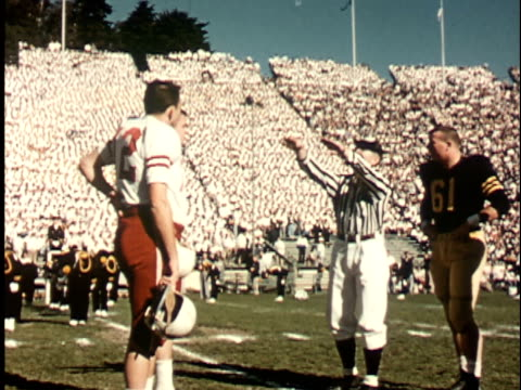vídeos de stock, filmes e b-roll de 1950s ws, referee tossing coin before american football match, california memorial stadium, berkeley, california, usa - lançar a moeda ao ar