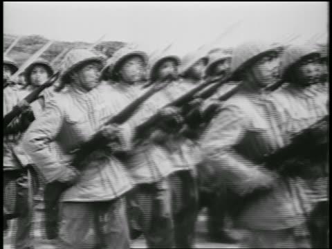 B/W 1950s PAN rows of soldiers carrying guns marching in parade / North Vietnam / newsreel