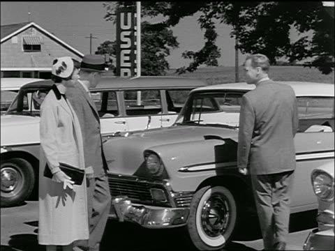 vidéos et rushes de b/w 1950s salesman showing chevrolet to couple at used car dealership - chevrolet