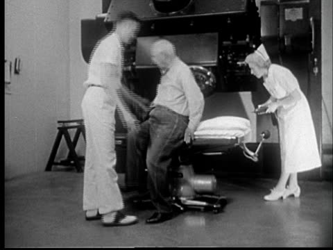 '1950s WS Senior man being helped into x-ray machine/ MS nurse aiming radiation instrument at man's chest/ St. Louis, Missouri'