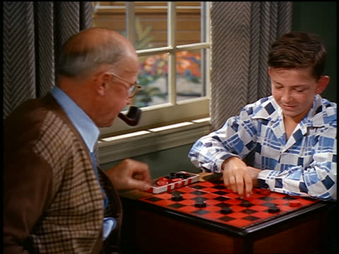 1950s senior man + boy playing checkers by window