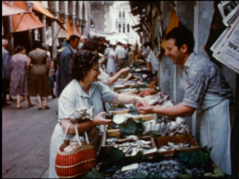 1950s senior woman paying + talking to male vendor for fresh fish at outdoor market / venice, italy - archival stock videos & royalty-free footage