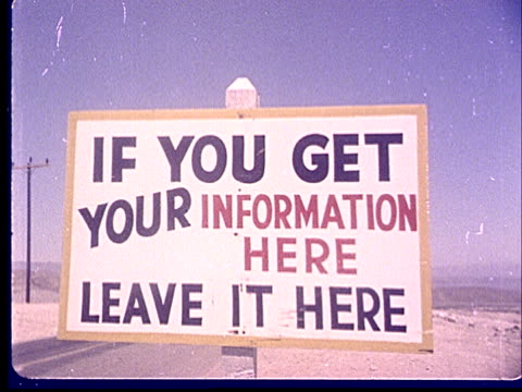 1950s MS Sign in desert reading 'If You Get Your Information Here Leave it Here' at Camp Desert Rock at Nevada Test Site / Nye County Nevada USA
