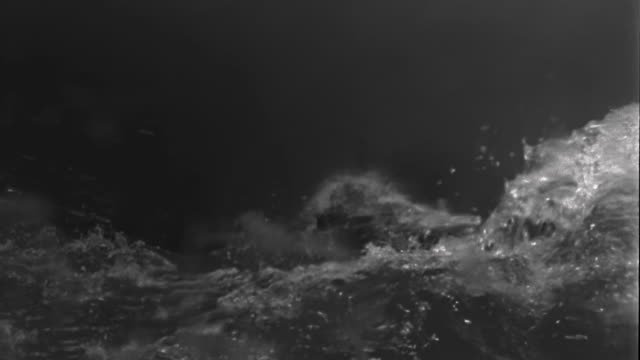 1950s slow motion medium shot ship moving over rough waters / staged - rough stock videos & royalty-free footage