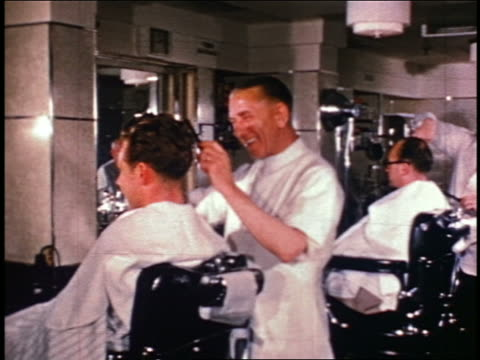1950s pan smiling barbers cutting hair of men in barbershop / industrial - barber stock videos & royalty-free footage
