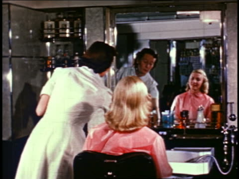 1950s smiling blonde woman looking in hand mirror as hairdresser combs hair in salon / industrial - 美容専門家点の映像素材/bロール